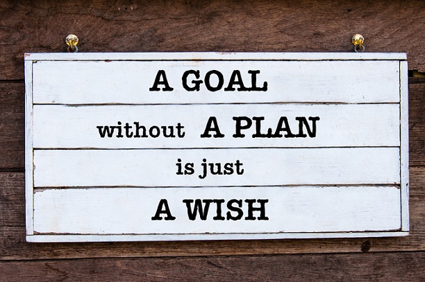 A Goal Without A Plan Is Just A Wish Inspirational message written on vintage wooden board. Motivational concept image